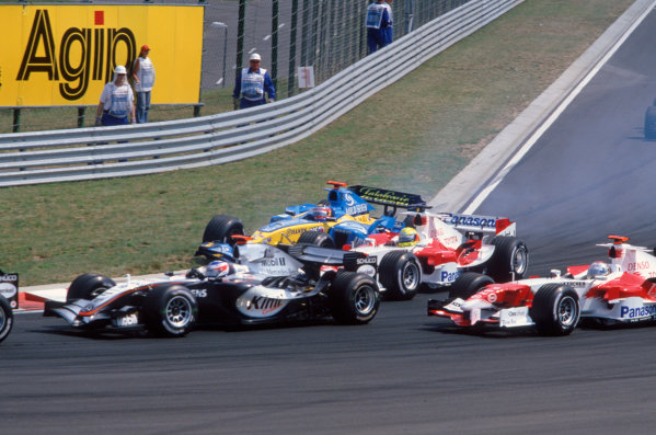 2005 Hungarian Grand Prix. Hungaroring, Hungary. 29th - 31st July 2005 Kimi Raikkonen, McLaren Mercedes MP4-20, Jarno Trulli, Toyota TF105 , Ralf Schumacher, Toyota TF105 and Fernando Alonso, Renault R25 battle for position going into turn 1 on the opening lap of the race. Action. World Copyright: Charles Coates/LAT Photographic Ref: 35mm Image A21