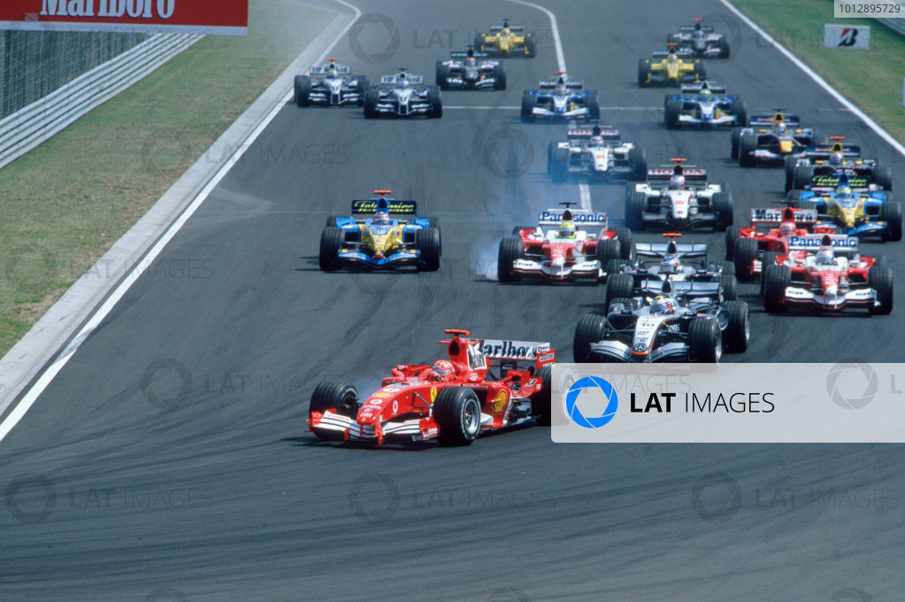 2005 Hungarian Grand Prix. Hungaroring, Hungary. 29th - 31st July 2005 Michael Schumacher, Ferrari F2005 leads the field into turn 1. Action. World Copyright: Charles Coates/LAT Photographic Ref: 35mm Image A11
