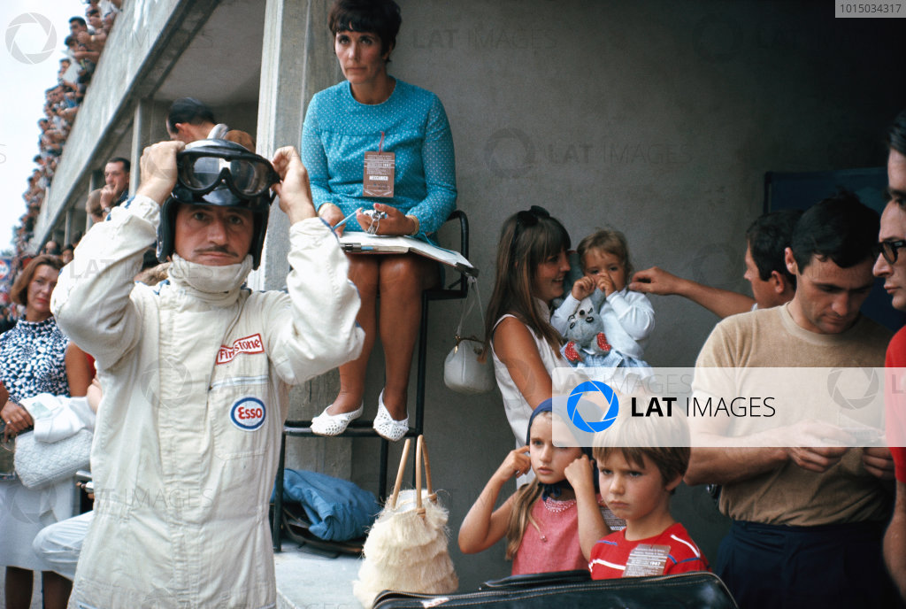 1967 Formula 1 World Championship. Italian Grand Prix. September 10, 1967. Graham Hill prepares for racing in the pits, surrounded by his family. His wife Bette Hill sits keeping time, above a nanny and three children - future Formula 1 World Champion Damon, and girls Samantha and Brigitte. World Copyright: Rainer Schlegelmilch/LAT Image ref: 67IT-Hill_Family-A3.jpg