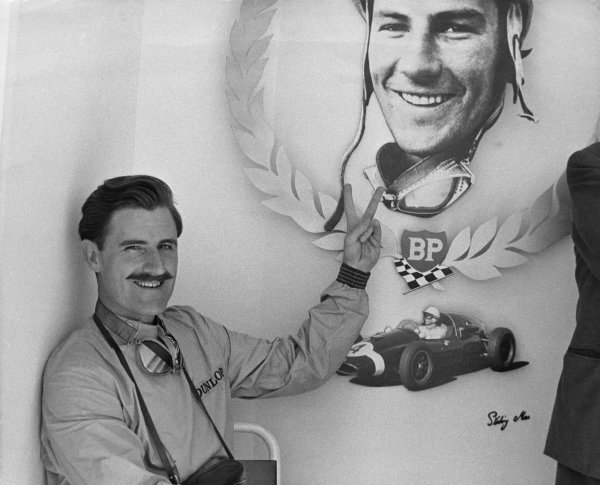 Monza, Italy. 13th September 1959.Graham Hill gives the victory sign to a Stirling Moss picture in the pits, portrait.World Copyright: LAT Photographic.Ref: B/W Print