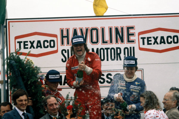 Zolder, Belgium. 3-5 June 1977. Gunnar Nilsson (Lotus 78-Ford), 1st position, celebrates with Ronnie Peterson (Tyrrell P34-Ford), 3rd position and Niki Lauda (Ferrari 312T2), 2nd position, podium, portrait.  World Copyright: LAT Photographic. Ref:  77BEL22