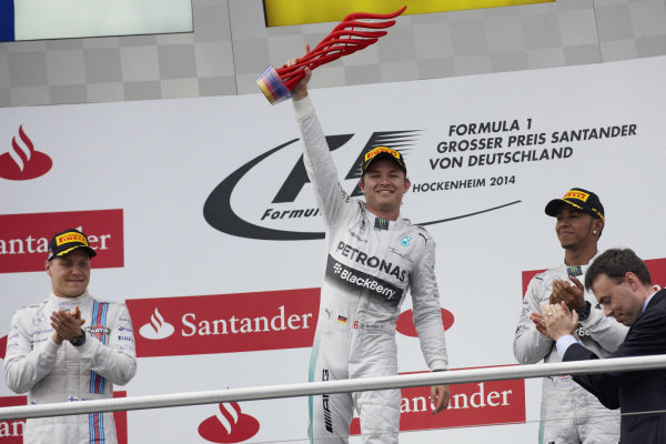Nico Rosberg, 1st position, celebrates on the podium alongside Valtteri Bottas, 2nd position, and Lewis Hamilton, 3rd position, on the podium.