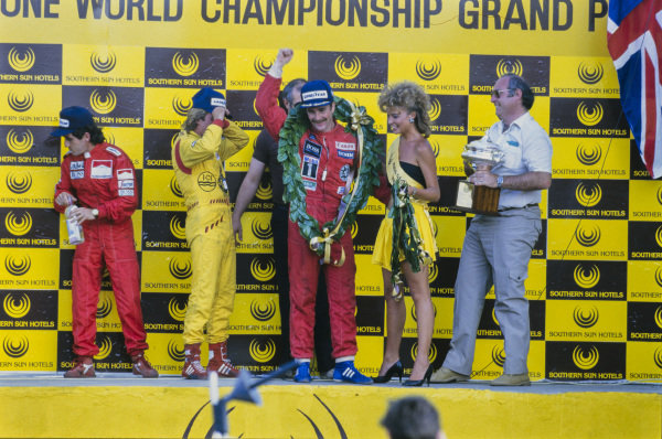 Nigel Mansell, 1st position, celebrates on the podium. Alongside are Keke Rosberg, 2nd position, and Alain Prost, 3rd position.