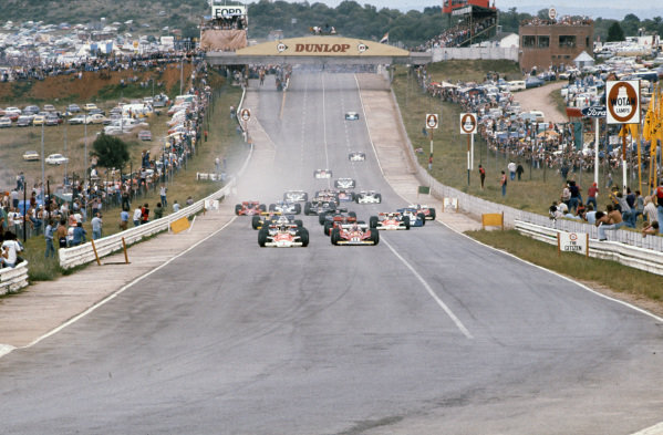 Pole sitter James Hunt, McLaren M23 Ford leads the field with Niki Lauda, Ferrari 312T2 alongside at the start.
