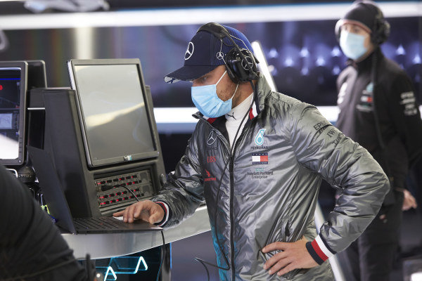 Valtteri Bottas wears a protective mask in the garage as he prepares to drive a Mercedes F1 W09.
