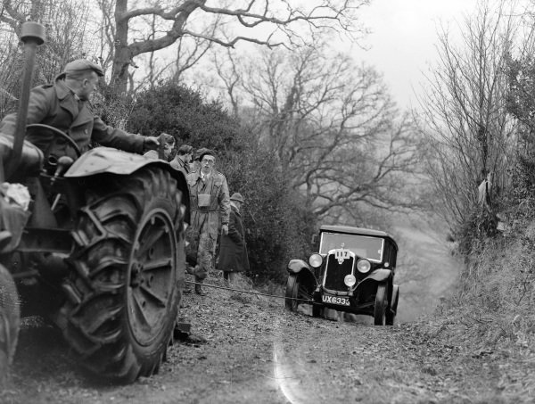 A car is towed uphill by a tractor.
