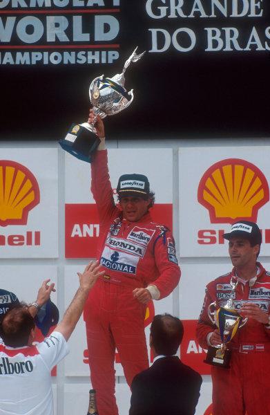 1991 Brazilian Grand Prix.Interlagos, Sao Paulo, Brazil.22-24 March 1991.Ayrton Senna (McLaren Honda) celebrates 1st position along with teammate Gerhard Berger (McLaren Honda) 3rd position and team boss Ron Dennis on the podium.Ref-91 BRA 08.World Copyright - LAT Photographic