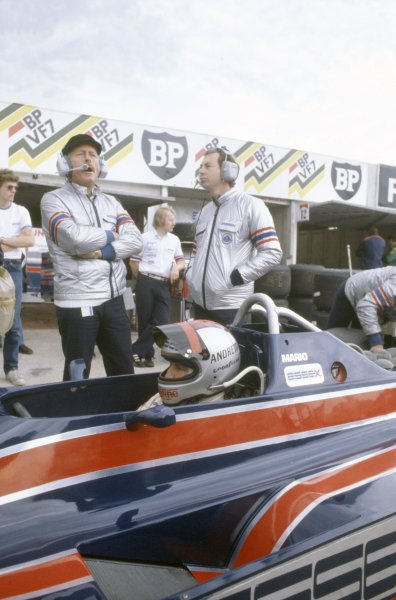 1980 British Grand Prix.Brands Hatch, Great Britain. 11-13 July 1980.Mario Andretti (Lotus 81-Ford Cosworth) in the pits with Colin Chapman and Peter Collins. Helmet, portrait.World Copyright: LAT PhotographicRef: 35mm transparency 80GB08