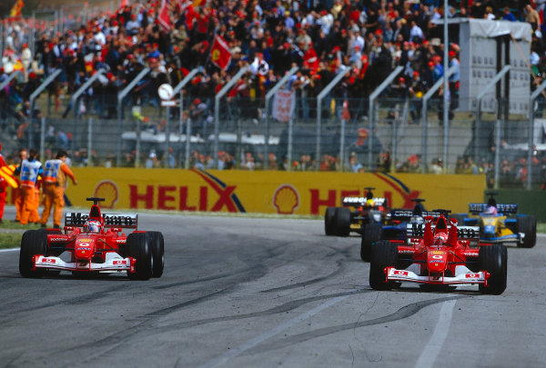 2002 San Marino Grand Prix.Imola, Italy.12-14 April 2002.Michael Schumacher (Ferrari F2002) punches the air to celebrate his 1st position with Rubens Barrichello also alongside.Ref-02 SM 26.World Copyright - LAT Photographic