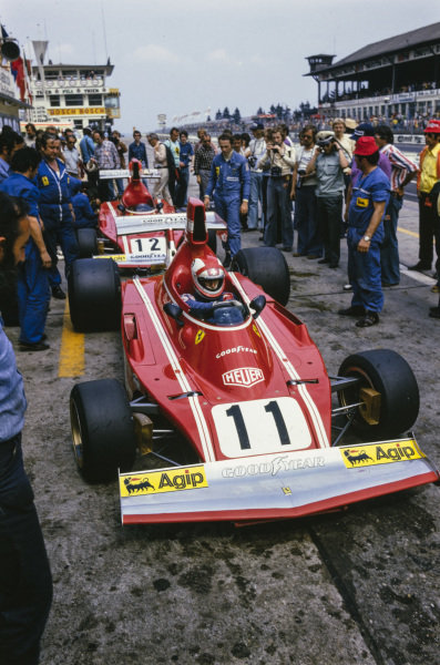 Clay Regazzoni, Ferrari 312B3 prepares to leave his pit, while Niki Lauda looks on.