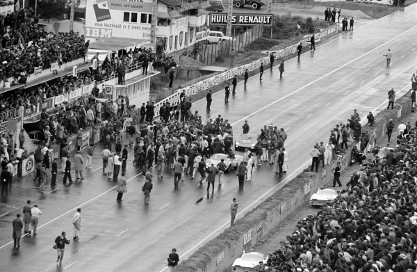 A crowd swamps Bruce McLaren / Chris Amon, Shelby American Inc., Ford Mk II, Ken Miles / Denis Hulme, Shelby American Inc., Ford Mk II, and Ronnie Bucknum / Richard Hutcherson, Holman & Moody, Ford Mk II, after the race.