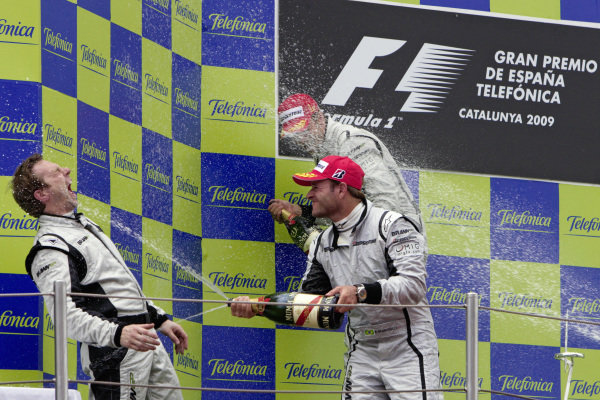 Jenson Button and teammate Rubens Barrichello spray engineer Matt Deane with champagne on the podium.