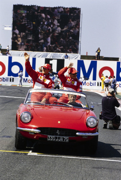 Michael Schumacher and Rubens Barrichello wave to the crowd on the drivers' parade.