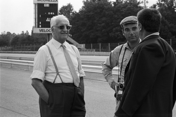 Enzo Ferrari and photographer Bernard Cahier talk in the pits.