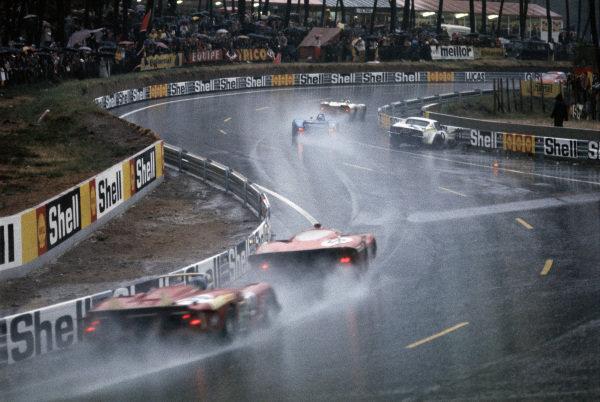 Cars pass the Jacques Bourdon / Jean-Claude Aubriet, Ecurie Léopard, Chevrolet Corvette wreckage, which rests against the guardrail after a crash in the rain.