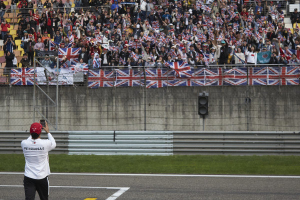 Lewis Hamilton, Mercedes AMG F1, takes a photo of his supporters