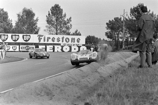 Robert Buchet / Herbert Linge, Philippe Farjon, Porsche 907/8, gets airborne as he hits the banking, as Jean-Luc Thèrier / Bernard Tramont, Sociètè des Automobiles Alpine, Alpine A210 - Renault R8 Gordini, follows behind.