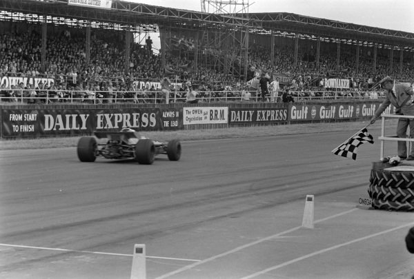 Jackie Stewart, Matra MS80 Ford, crosses the line and takes the chequered flag.
