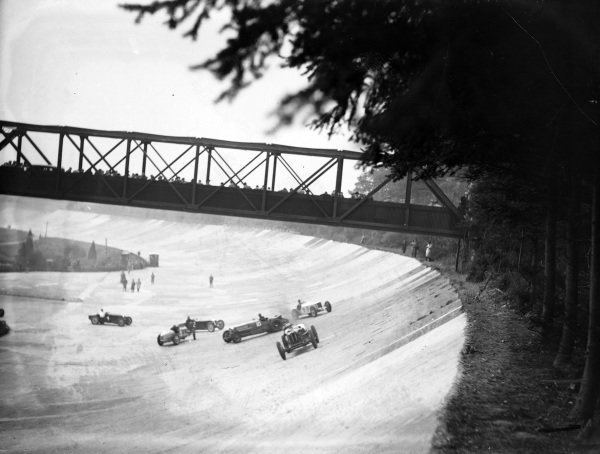 Brian Lewis, Alfa Romeo Monza, drives away as Malcolm Campbell, Sunbeam Tiger, and Tim Rose-Richards, Bugatti T51, both spin behind.
