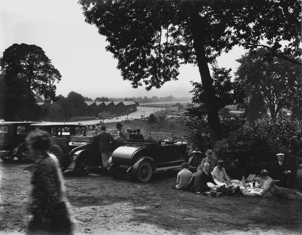 Brooklands, England. 25th - 27th August 1928.Cars line up in front of the Vickers sheds as the crowd enjoys a picnic.Ref: B360World Copyright: LAT Photographic.