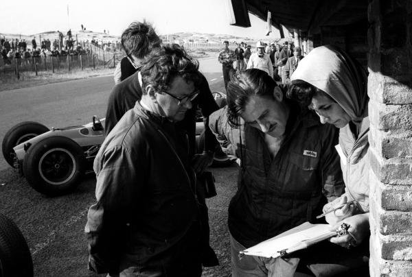 (L to R): Tony Rudd BRM Chief Designer; Graham Hill and his wife Bette study the lap timings of the new BRM P61 monocoque that was used for the first time during practice but not raced. Dutch Grand Prix, Zandvoort, 23 June 1963.