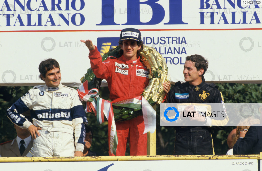 1985 Italian Grand Prix. Monza, Italy. 6th - 8th September 1985. Alain Prost (McLaren MP4/2B-TAG Porsche) 1st position, celebrates with Nelson Piquet (Brabham BT54-BMW) 2nd position and Ayrton Senna (Lotus 97T-Renault) 3rd position, on the podium, portrait. World Copyright: LAT Photographic. Ref: 85ITAb