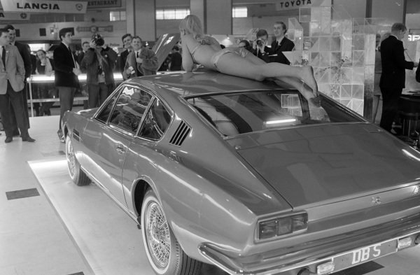 Photographers shoot a model on the roof of an Aston Martin DBS.
