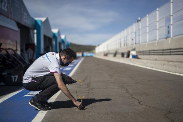 A Mercedes Benz EQ team member measures the temperature of the track