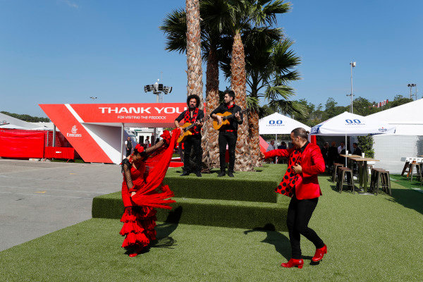Spanish guitarists and dancers in traditional costume perform at the entrance to the paddock.