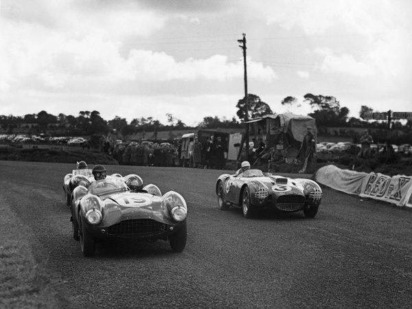 Dundrod, Northern Ireland. 11 September 1954 Graham Whitehead/Dennis Poore (Aston Martin DB3S), 8th position leads Piero Taruffi/Juan Manuel Fangio (Lancia D24), 2nd position,  action. World Copyright: LAT Photographic Ref: B/W Print