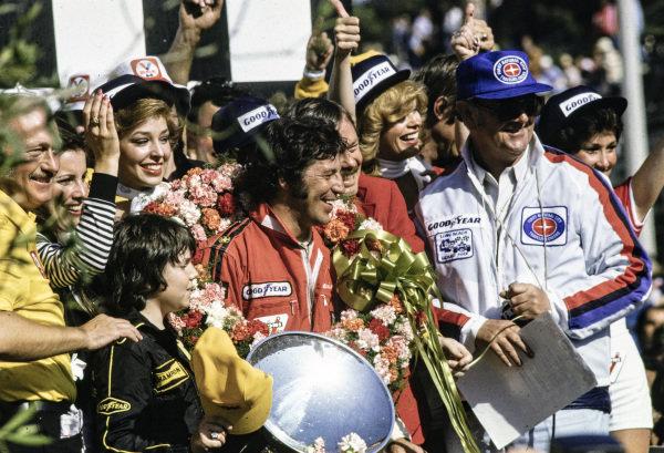 Race winner Mario Andretti on the podium.