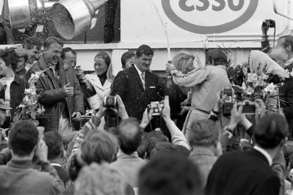 The 2.0 class winners of Jo Siffert and Hans Hermann celebrate their victory on the right by spraying champagne, while outright winner Dan Gurney and AJ Foyt look on with second placed Mike Parkes.