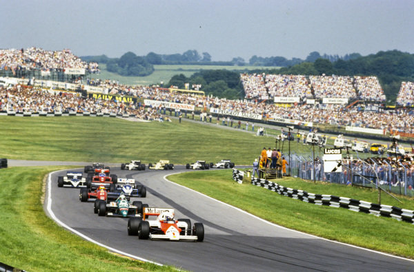 Alain Prost, McLaren MP4-2C TAG, leads Teo Fabi, Benetton B186 BMW, Michele Alboreto, Ferrari F1/86, and René Arnoux, Ligier JS27 Renault.
