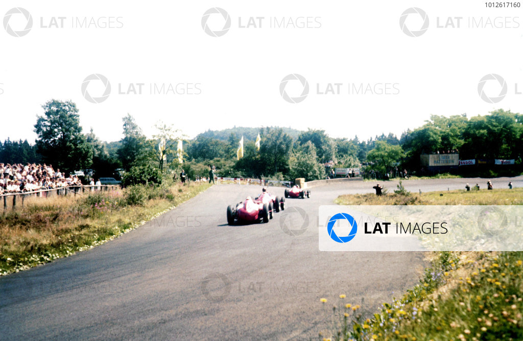 Nurburgring, Germany.2-4 August 1957.Juan Manuel Fangio (Maserati 250F) between Mike Hawthorn and Peter Collins (both Lancia-Ferrari D50 801). They finished in 1st, 2nd and 3rd positions respectively.Ref-57 GER 20.World Copyright - LAT Photographic