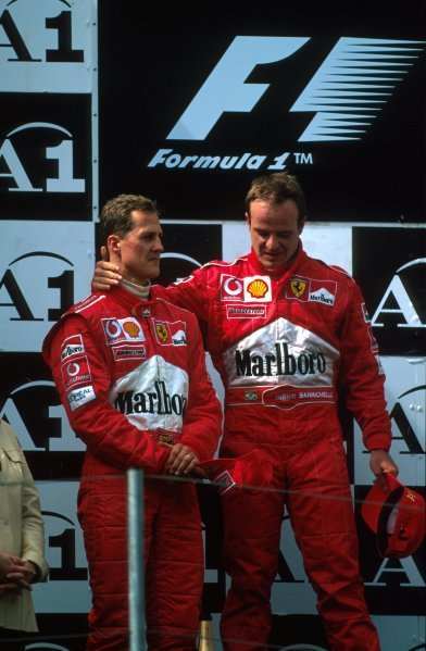 Michael Schumacher (GER) and Rubens Barrichello (BRA) find themselves unsure how to react on the podium after the contrived finish forced upon them by the Ferrari team management.