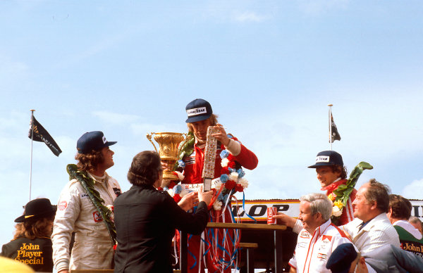 """1977 British Grand Prix.Silverstone, England.14-16 July 1977.James Hunt (McLaren Ford) 1st position, Niki Lauda (Ferrari) 2nd position and Gunnar Nilsson (Lotus Ford) 3rd position on the podium. McLaren team manager Edward """"Teddy"""" Mayer stands at the front.Ref-77 GB 11.World Copyright - LAT Photographic"""