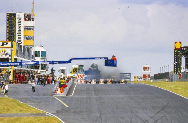 Teo Fabi, Toleman TG185 Hart, Alain Prost, McLaren MP4-2B TAG, Stefan Johansson, Ferrari 156/85, and Keke Rosberg, Williams FW10 Honda, lead the field off the line at the start.