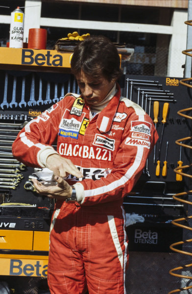 Gilles Villeneuve cleans his visor in the pitlane.
