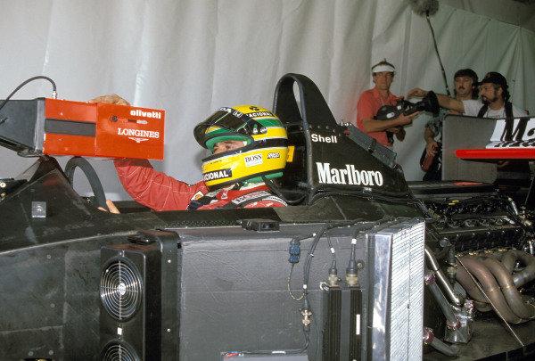 Ayrton Senna sits in his McLaren MP4-6 Honda and consults a monitor.