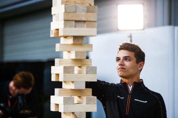 Lando Norris, McLaren, plays a game of giant Jenga