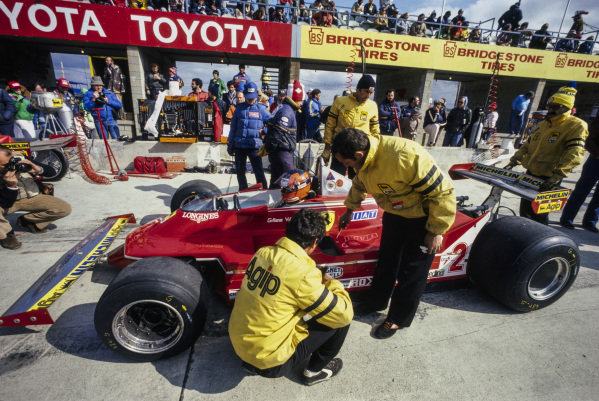 Gilles Villeneuve, Ferrari 312T5, has his car worked on in the pits.