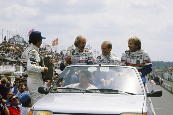 Le Mans, France. 31st May - 1st June 1986.Hans-Joachim Stuck /Derek Bell /Al Holbert (Porsche 962C), 1st position, are serenaded by Dieter Quester on the drivers parade, portrait. World Copyright: LAT PhotographicRef: 86LM