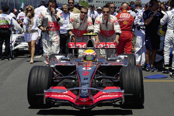 Mechanics push Lewis Hamilton in his McLaren MP4-22 Mercedes to pole position on the grid.
