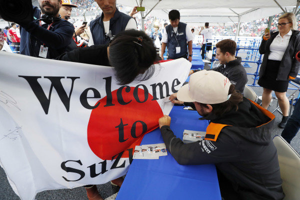 Fernando Alonso, McLaren, signs a huge Japanese flag with a message from fans
