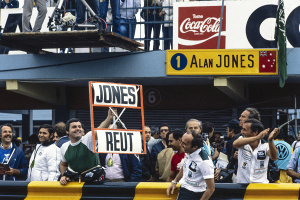 Alan Jones holds out a pit board showing that he is ahead of Carlos Reutemann. Frank Williams and other team members laugh.