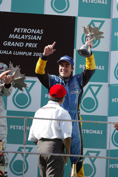 2003 Malaysian Grand Prix. Sepang, Kuala Lumpur, Malaysia.21-23 March 2003.Fernando Alonso (Renault) celebrates his 3rd position on the podium.World Copyright - Steve Etherington/LAT Photographic ref: Digital Image Only