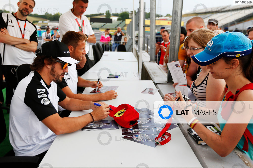 Hungaroring, Budapest, Hungary. Thursday 23 July 2015. Fernando Alonso, McLaren, and Jenson Button, McLaren, sign autographs for fans. World Copyright: Charles Coates/LAT Photographic ref: Digital Image _N7T1941