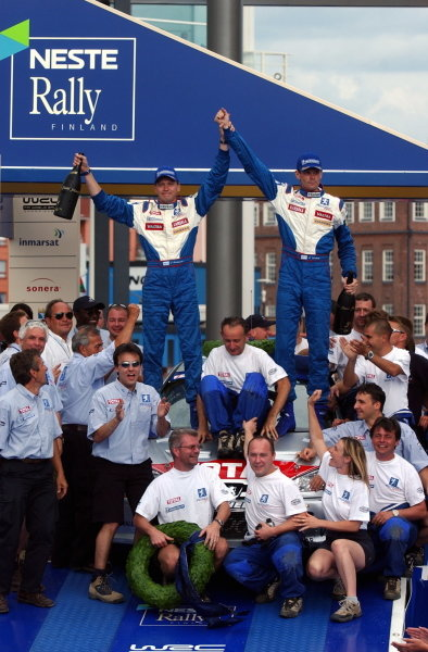 Rally winner Marcus Gronholm (FIN) and team mate Timo Rautiainen (FIN) Peugeot 206 WRC celebrate on the podium. FIA World Rally Championship, Rd9, Neste Rally Finland, Day Three, Finland. 11 August 2002. DIGITAL IMAGE