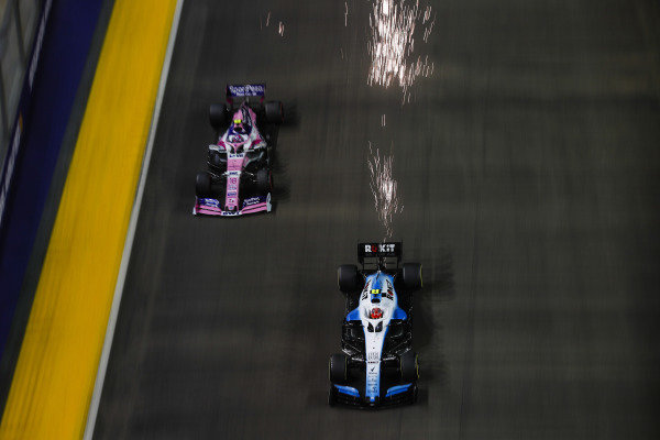 Robert Kubica, Williams FW42, passes Lance Stroll, Racing Point RP19, with a shower of sparks