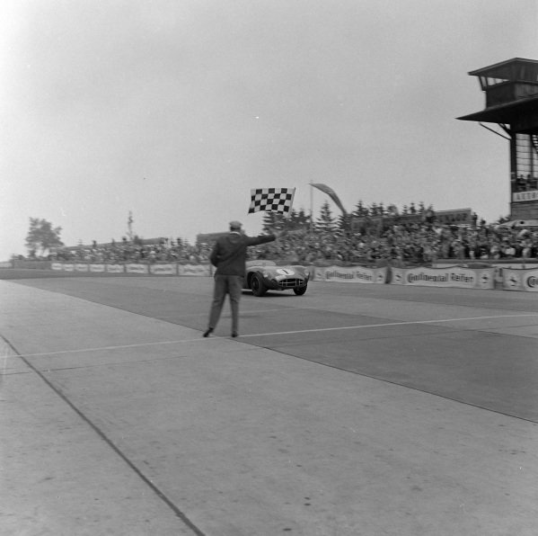 Stirling Moss / Jack Fairman, David Brown, Aston Martin DBR1/300, crosses the finish line and takes the chequered flag for victory.